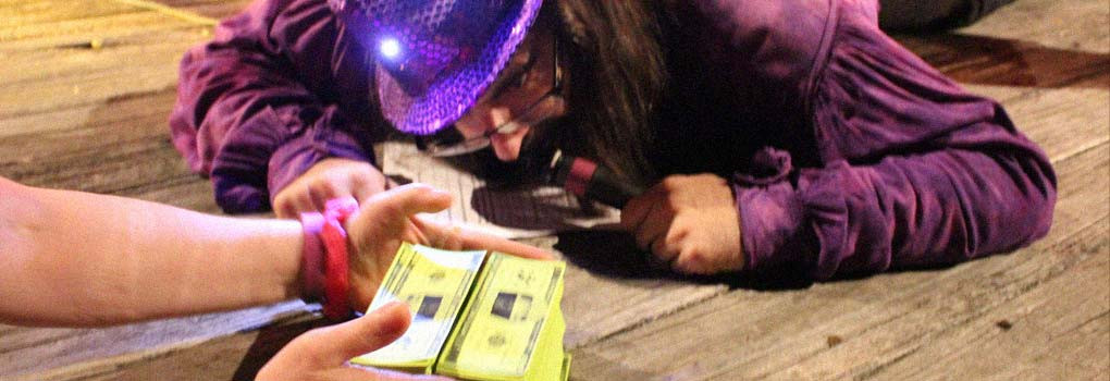 Bo gets down on the stage to closely examine 2 stacks of play money, while wearing a sparkly purple hat.