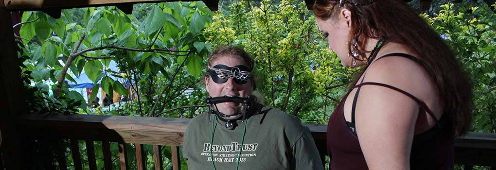 A man wearing a bit gag and blindfold is menaced by a very femme lady in the lower dungeon, with leafy trees in the background