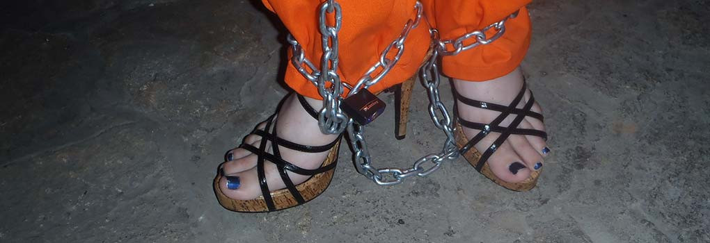a woman's feet in pretty high heeled sandals, wearing an prison jumpsuit and chains around her ankles.