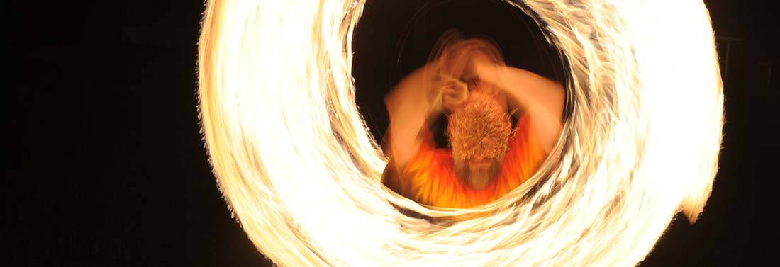 a man on an openwork metal greeenman mask spins fire at night