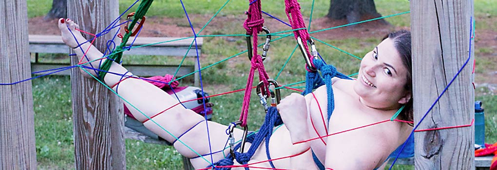A dark haired smiling girl is suspended outdoors, in blue and red rope