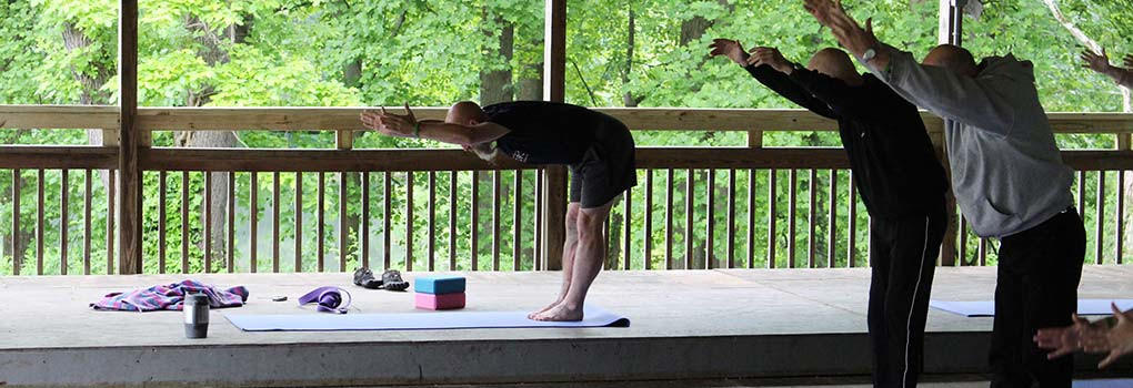 An instructor leads morning yoga class in the dance pavillion