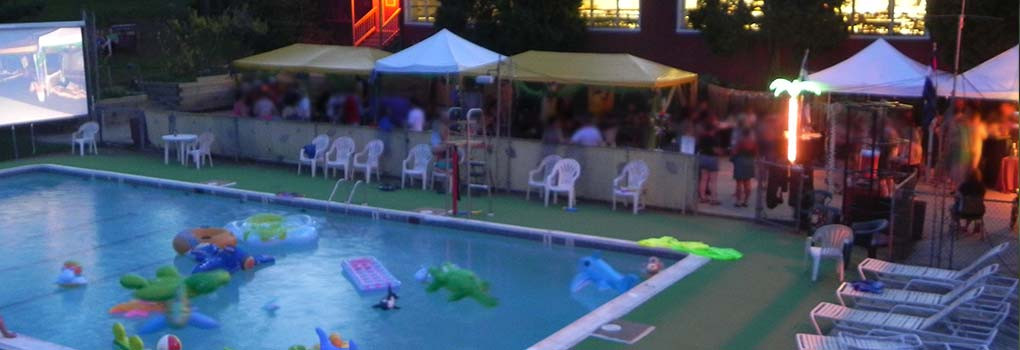 an evening pool party, with lots of inflatable toys in the pool and some very blurry people enjoying cocktails