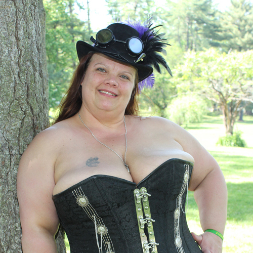 smiling woman in corset with fancy hat