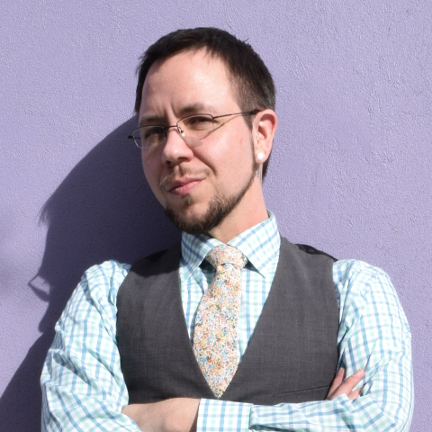 A sharply dressed man with a serious expression leans agains a purple wall