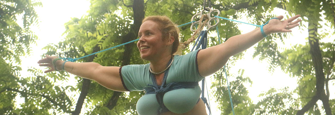 happy woman in a blue top suspended in a tree