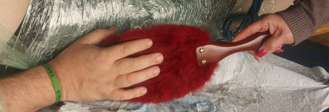 a hand pets a fur paddle held by another hand with red nails